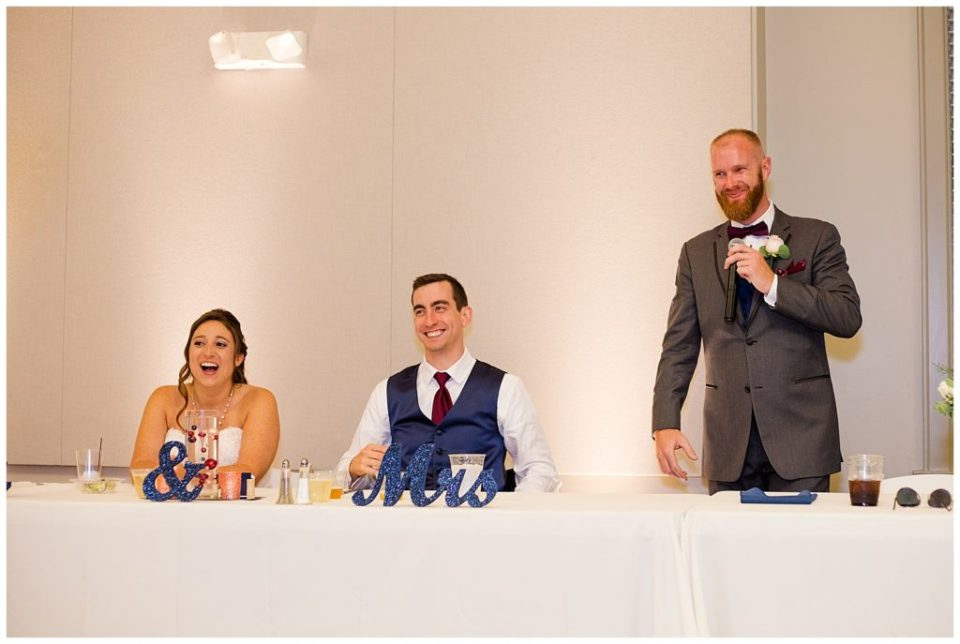A photograph of the best man standing at the wedding party table, giving his speech at the wedding reception at a Station 67 Columbus Ohio wedding by Alayna Parker Photography