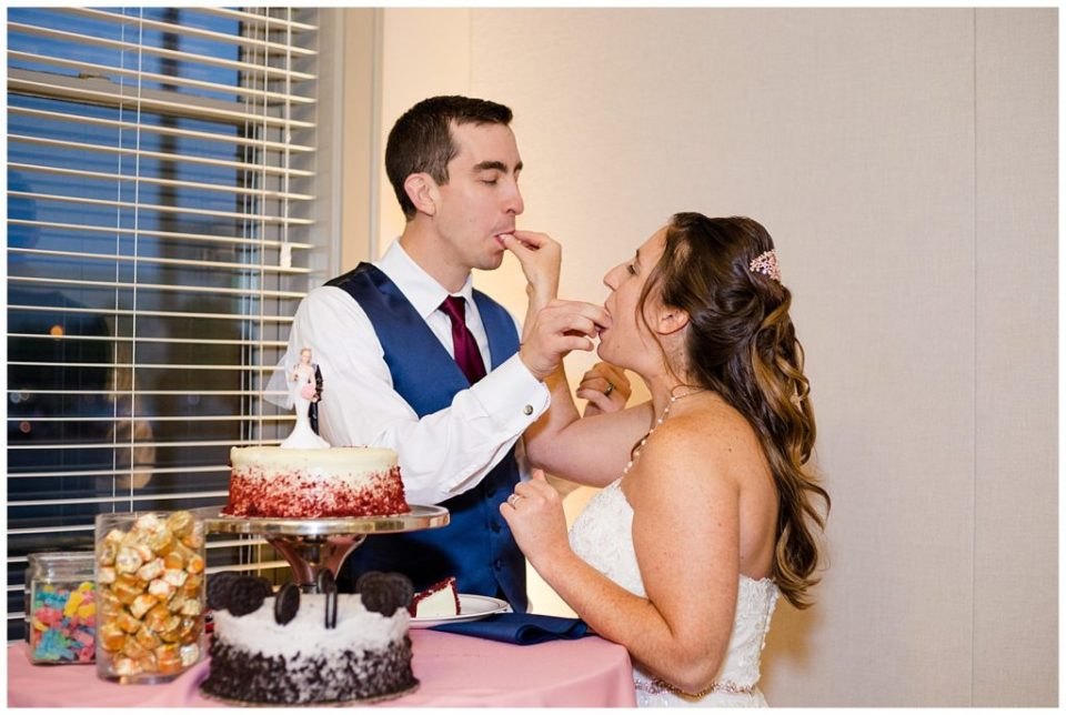 A photograph of the bride and groom feeding each other a bite of wedding cake at their reception at a Station 67 Columbus Ohio wedding by Alayna Parker Photography