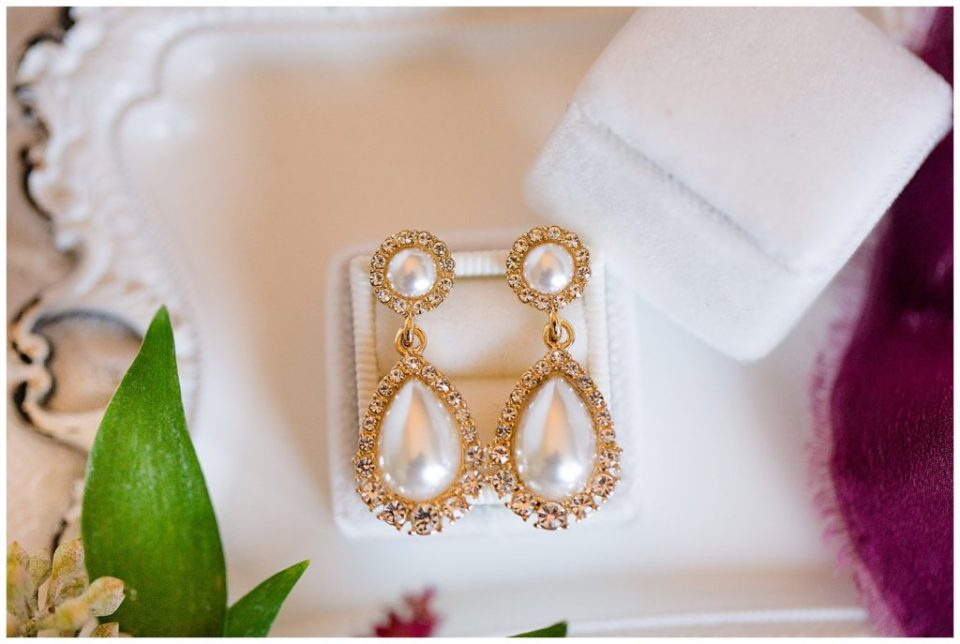An image of a closeup of the bride's earrings before she puts them on for her wedding by Columbus Ohio wedding photographer, Alayna Parker Photography