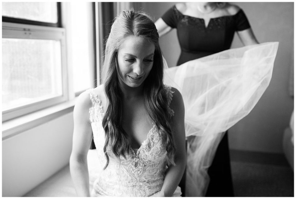 black and white image of mom fluffing brides veil at renaissance hotel