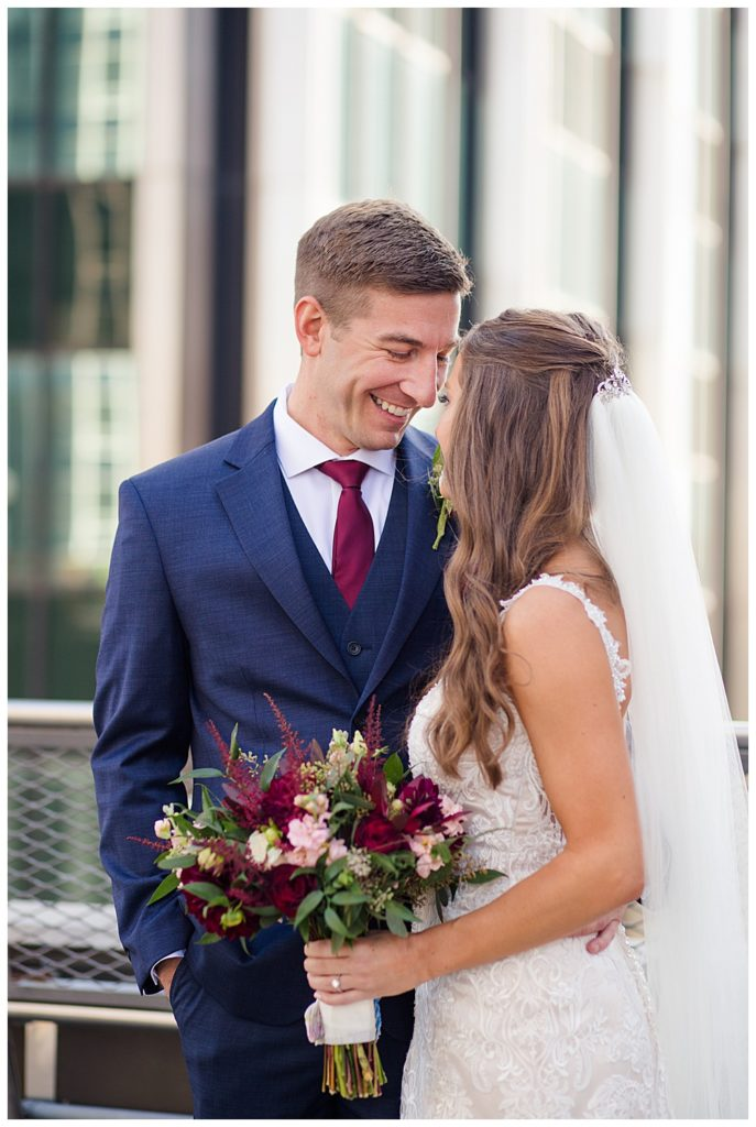 Groom smiling at bride on rooftop at renaissance hotel