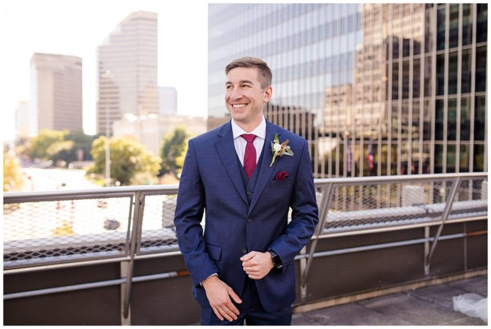 groom smiling off in the distance on rooftop at renaissance hotel
