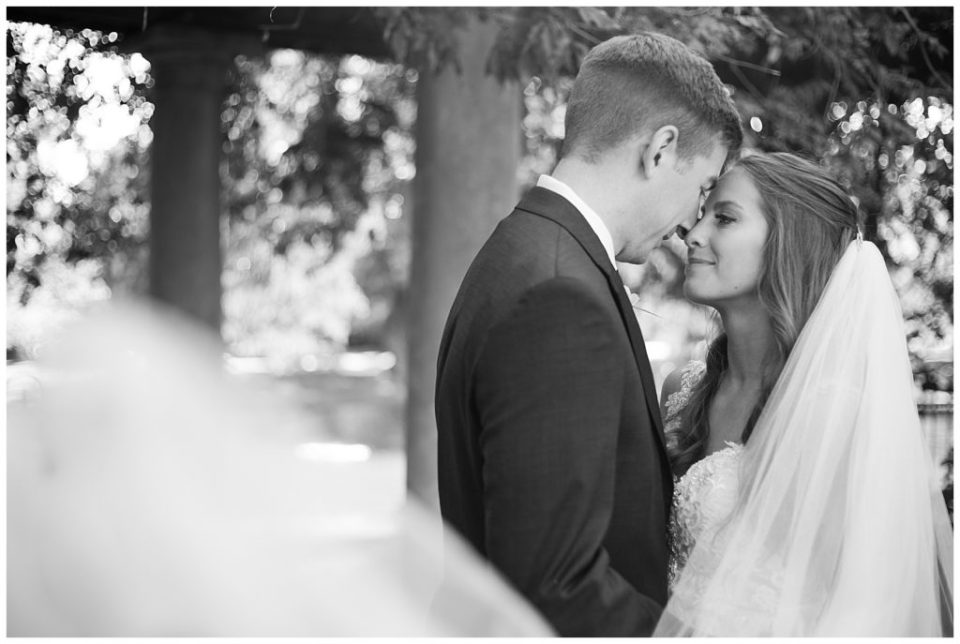 black and white image of bride and groom touching foreheads at schiller park in german village