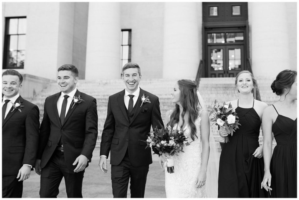 black and white image of groom smiling at camera while walking with bridal party outside ohio statehouse