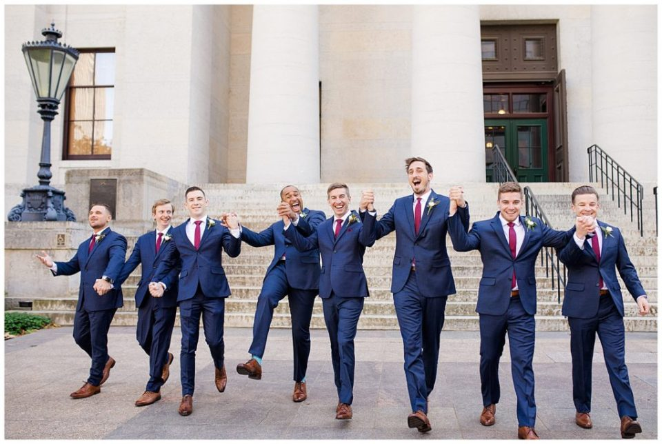 groom and groomsmen holding hands and skipping outside ohio statehouse