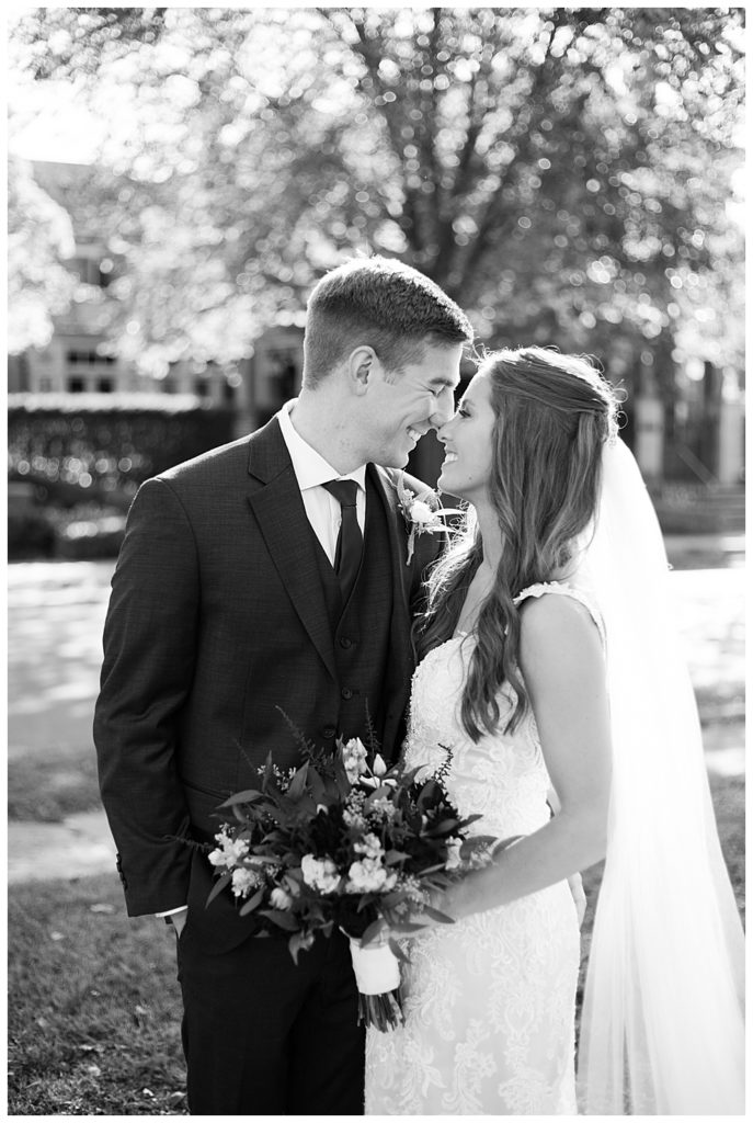 black and white image of bride and groom touching noses at schiller park in german village
