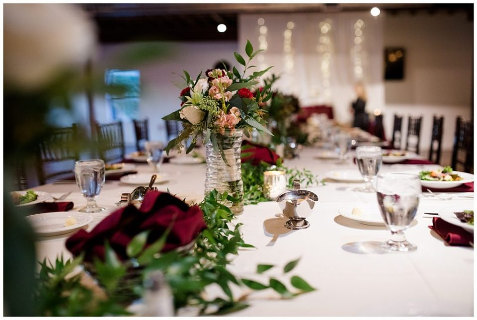 bouquets in glass vases on head table at copius