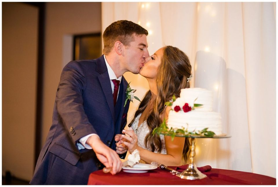 bride and groom share kiss after cutting cake at copius