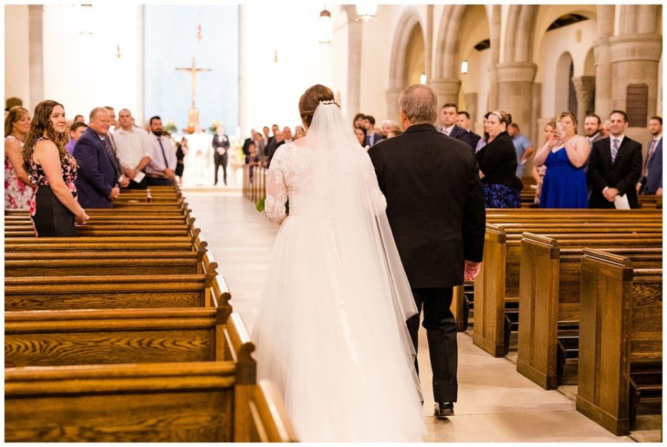 An image of the bride and her father walking down the aisle in church as the wedding guests turn to watch at a Nationwide Hotel and Conference Center wedding by Columbus Ohio wedding photographer, Alayna Parker Photography