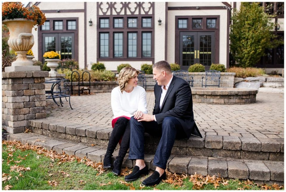 An image of an engaged couple holding hands, sitting outside on brick steps, smiling and gazing at each other at Brookside Golf & Country Club by Columbus Ohio engagement photographer, Alayna Parker Photography