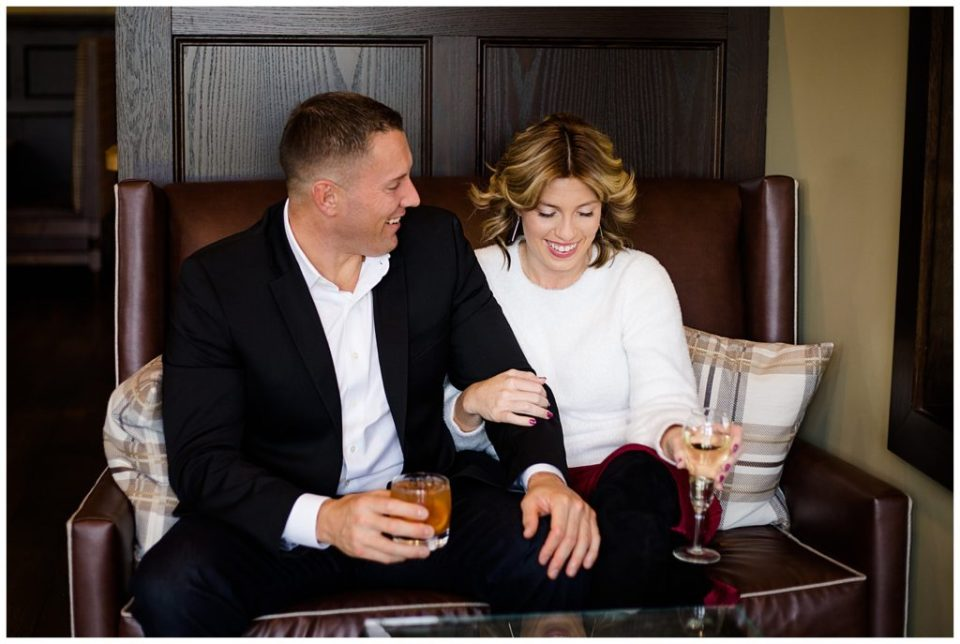 An image of an engaged couple sitting close, relaxed and smiling as they enjoy cocktails at Brookside Golf & Country Club by Columbus Ohio engagement photographer, Alayna Parker Photography