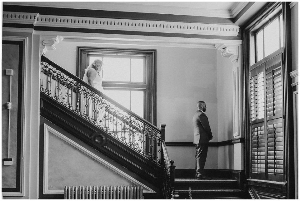 black and white image of bride walking down staircase to see groom at the postmark