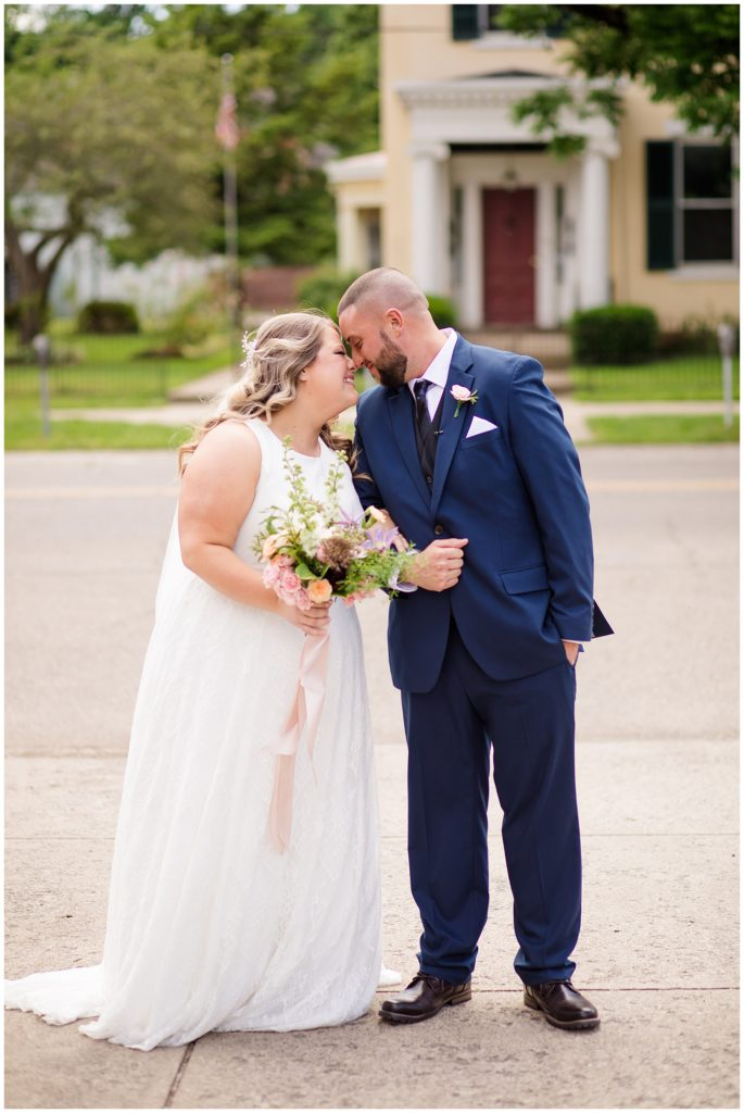 bride and groom smiling and touching foreheads outside at the postmark
