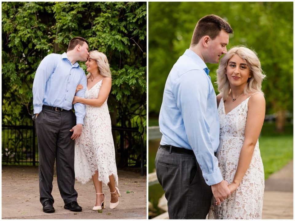 A picture of a newly engaged couple standing close as the woman, wearing a lovely lace dress, grasps her fiance's arm and he leans over to tenderly kiss her forehead by Alayna Parker Photography an engagement photography in Columbus
