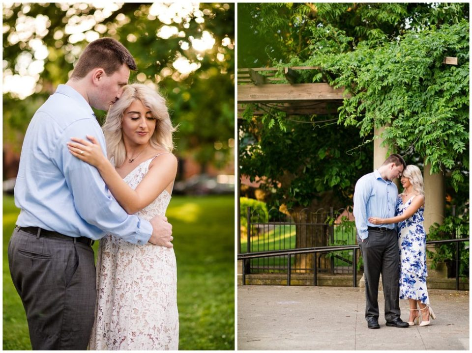 An image of a couple who are recently engaged pausing as they share an embrace and the man gently leans down to touch his fiancee's long blonde hair at Schiller Park to the east of the brewery District in Columbus Ohio