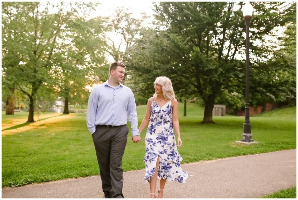 An image of a couple walking through a lush, green park, hand in hand, lovingly gazing at each other as they share time after recently becoming engaged by Alayna Parker an engagement photography in Columbus