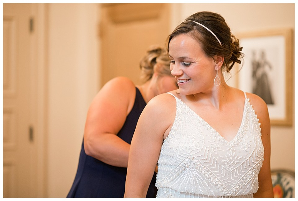 A photograph of a closeup view of the bride smiling and looking back toward her sister who is closing the back of her wedding dress by Alayna Parker - Columbus Ohio wedding photography