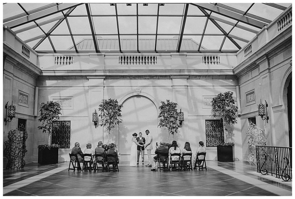 A picture in black and white of a long-distance view of a wedding ceremony in a spacious, elegant museum room with a huge skylight overhead by Alayna Parker - Columbus Ohio wedding photographer