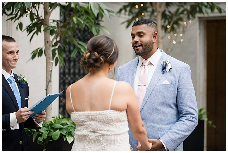An image of the groom repeating his vows to his bride as they face each other, holding hands, while the preacher stands nearby in the Columbus Museum of Art