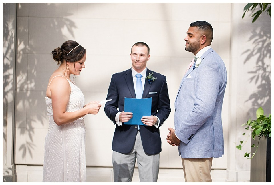 An image of a bride reading her vows to her groom as they stand with the preacher during their wedding ceremony by Alayna Parker - Columbus Ohio wedding photographer