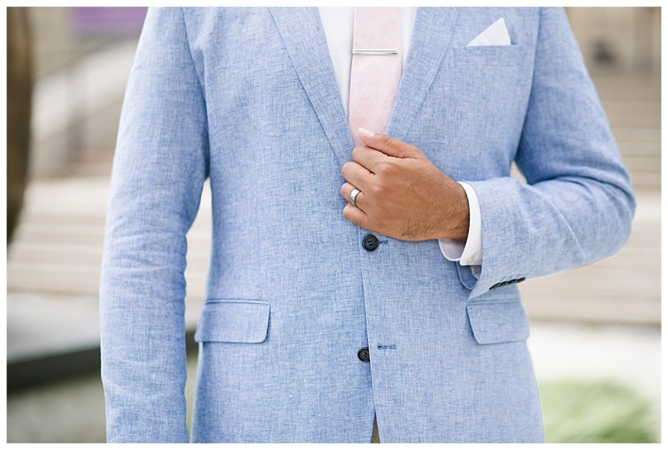 A picture of a closeup view of the groom adjusting his blue jacket and pink tie while his wedding ring is clearly seen in the Columbus Museum of Art on E Broad St, Columbus Ohio
