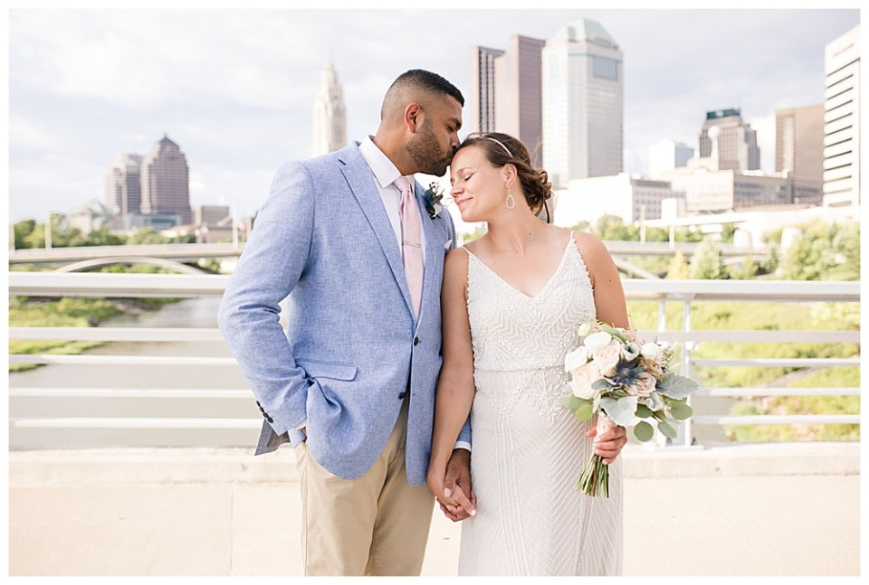 A picture of a bridal couple standing close, holding hands as the groom tenderly kisses his bride's forehead with the city skyline behind them at the Columbus Museum of Art in downtown Columbus