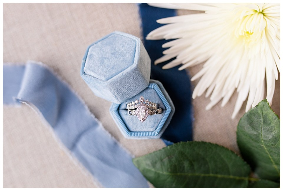 An image closeup of the bride's rings in the jewelry box near blue ribbons and a flower with greenery at Dorral Farm in Marysville, OH