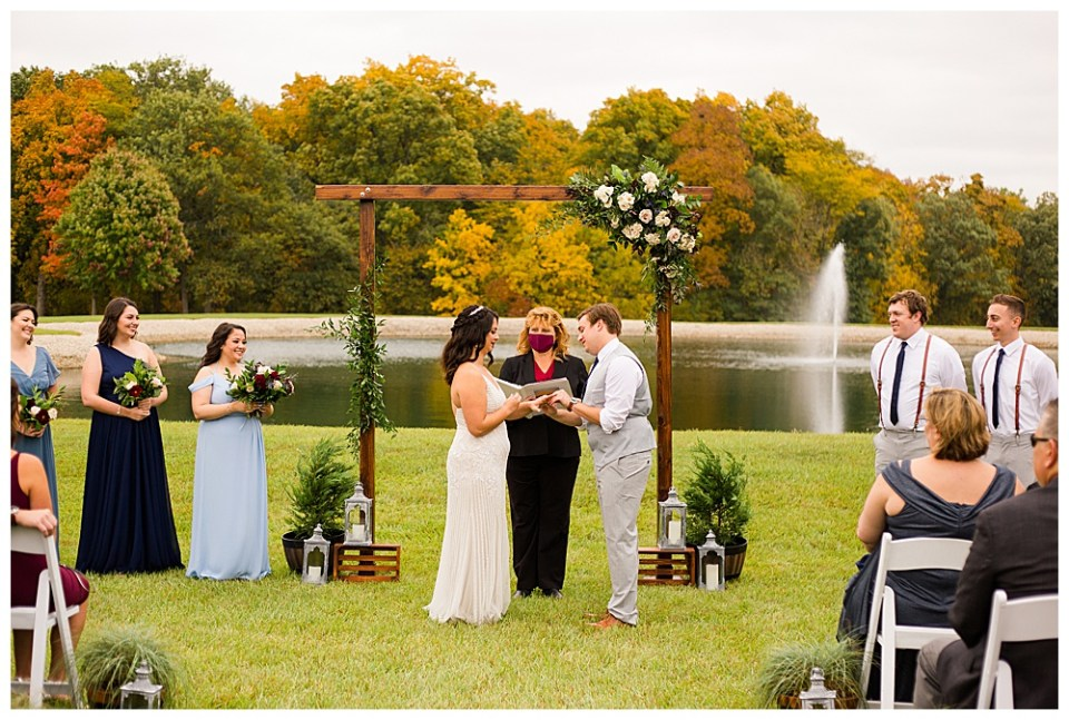 A picture of the bride and groom exchanging rings during the wedding ceremony near the wedding arch, the officiant, and the wedding party as they stand outdoors in front of a lovely fall setting
