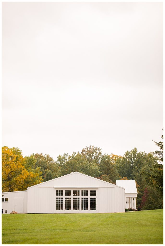 An image of the wedding reception venue from the outside, showing a picturesque line of windows with a background of fall trees