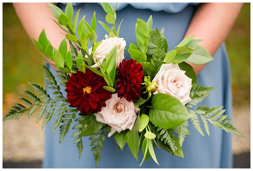 A photograph of a closeup view of the bridesmaid's exquisite bouquet of red and white flowers with delicate greenery by Alayna Parker a Columbus Ohio wedding photographer