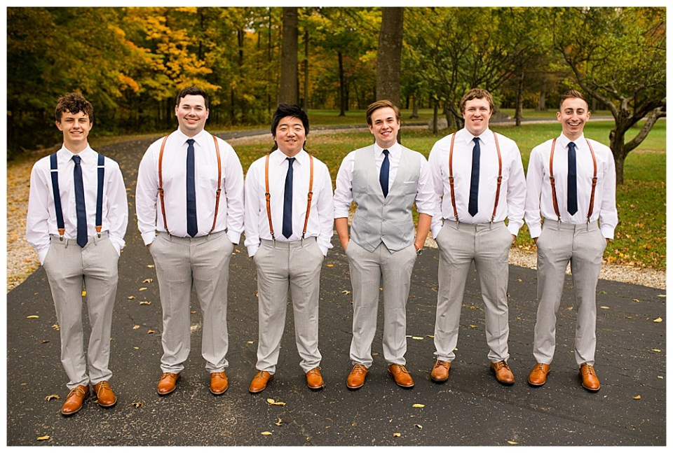 A picture of the groom and his groomsmen lined up smiling together as they stand outdoors after the wedding