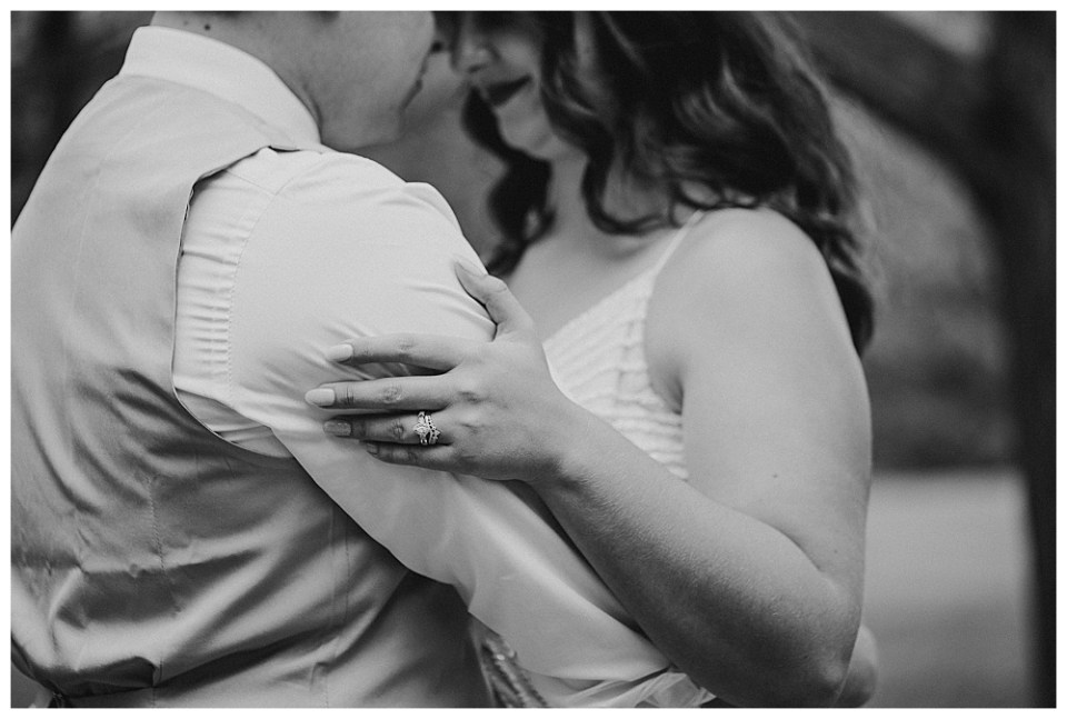 An image in black and white of the bride and groom closeup as they tenderly embrace in a quiet moment together