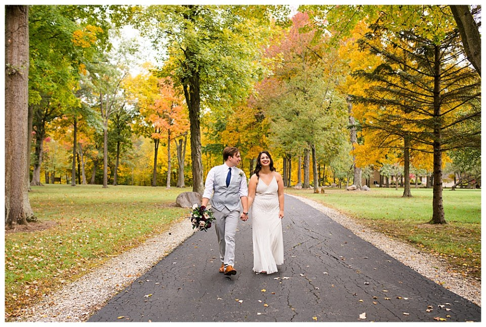 A picture of a long-distance view of the bride and groom holding hands, walking down a quiet park road with the trees behind them showing lovely fall colors