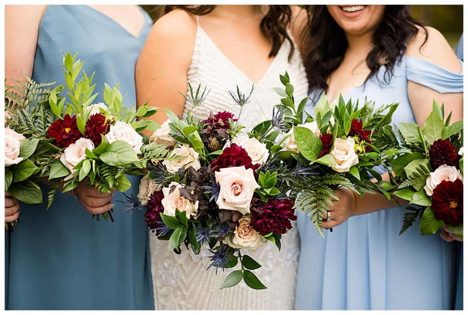 A picture showing a close view of the bouquets of the bride and bridesmaids as they stand together with their stunning flowers and greenery by Alayna Parker Photography a Columbus Ohio wedding photographer