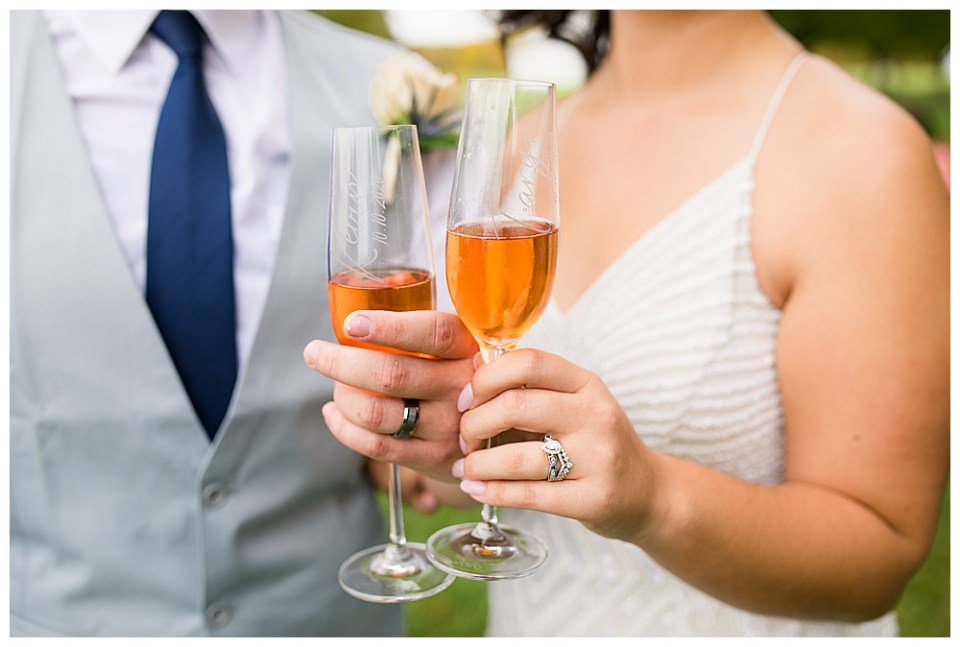 A photograph of a closeup view of the bride and groom holding their glasses of wine, toasting at their wedding reception, showing off their new wedding rings