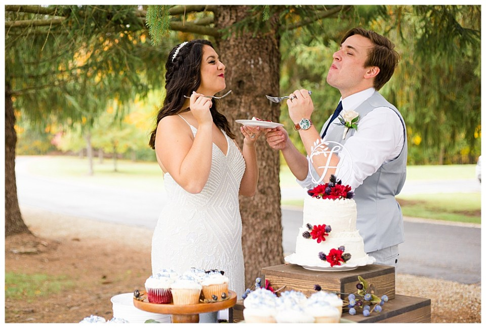 An image of the bride and groom tasting the first bite of their wedding cake, each experiencing the same yummy joy as they stand outside at their wedding reception