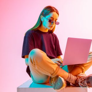 Modern Girl with laptop, tablet computer. Free creativity. Young blogger makes a Home office. Colored Neon light and background.