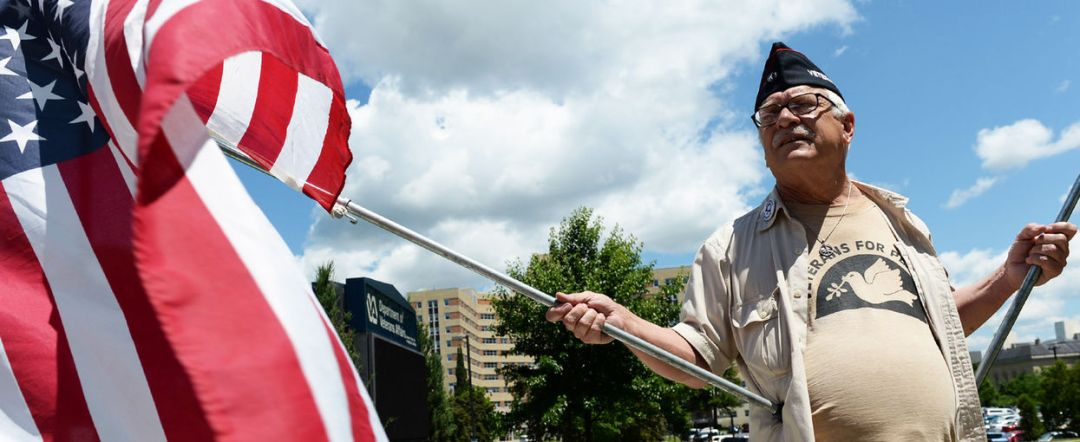 Dan Wilcox, of Albany holds flags in front of the Stratton VA Medical Center
