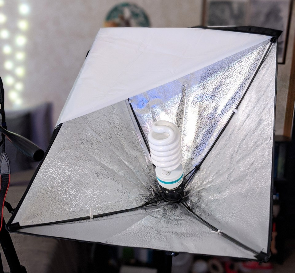 A black softbox light with the diffuser open so the bulb is revealed