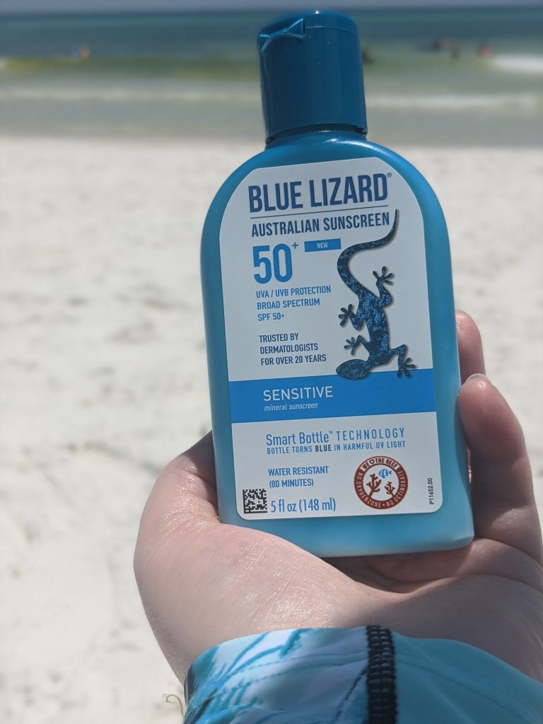 A bottle of BLue Lizard sunscreen with a beach view out of focus behind it.
