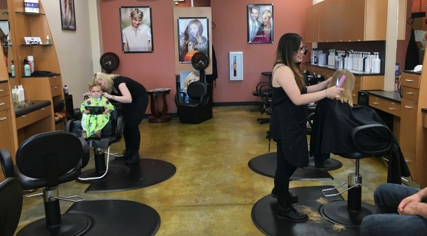 Brother and Sister getting a haircut in the empty salon.