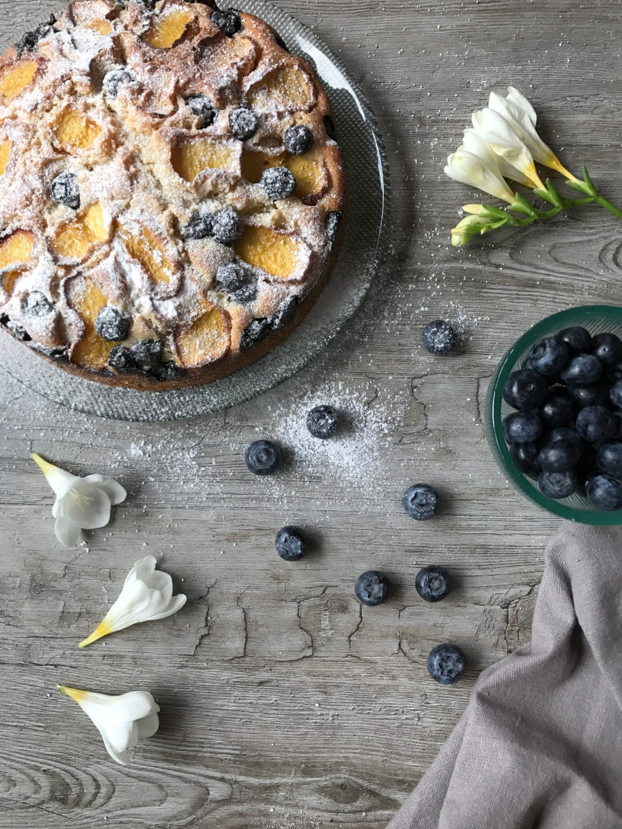 Overhead shot of a peach cake with blueberries and freesias on the table