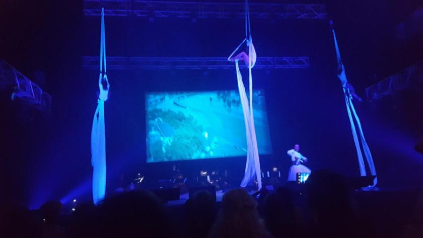 Aerialists and musicians perform in front of large screen displaying historical events