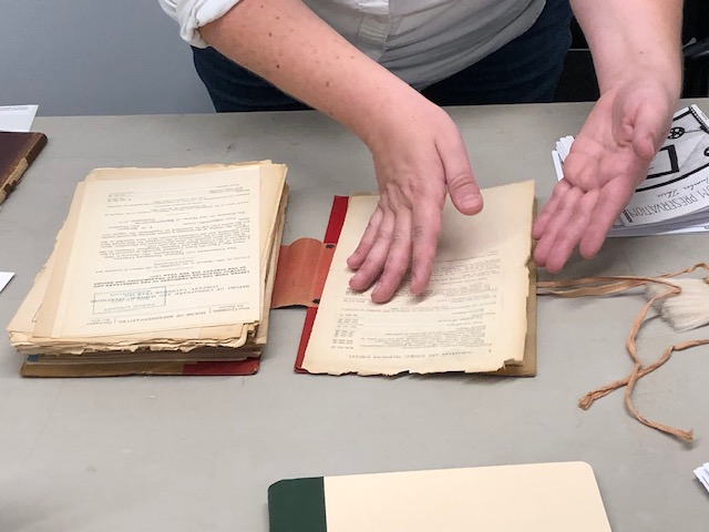 A person's hands open a bundle of archival materials tied with string.