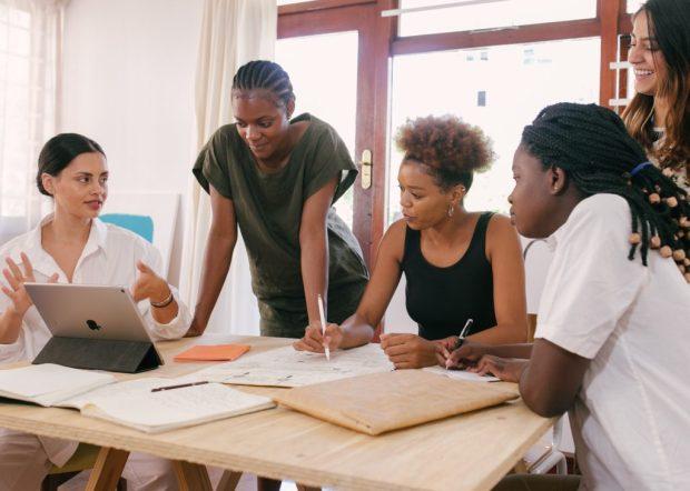 várias mulheres negras em uma reunião de negócios, sentadas em uma mesa com computador e cadernos