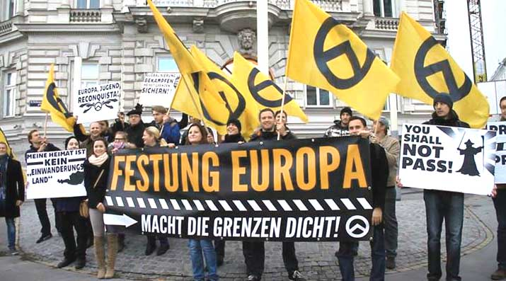 "Far-right activists at an Identitarian Movement of Austria anti-immigration rally in Vienna. The German-language signs read ""Fortress Europe"", ""Close the Borders Now!"", ""My Home is Not an Immigrant Country"", and ""Europe, Youth, Reconquista""."