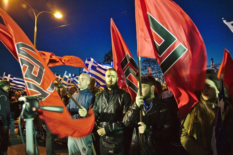 Miembros de amanecer Dorada sostienen banderas en un mitin fuera de la sede general del partido en Atenas, 2015. Autor: DTRocks, 21/03/2015. Fuente: Wikimedia Commons. (CC BY-SA 4.0)