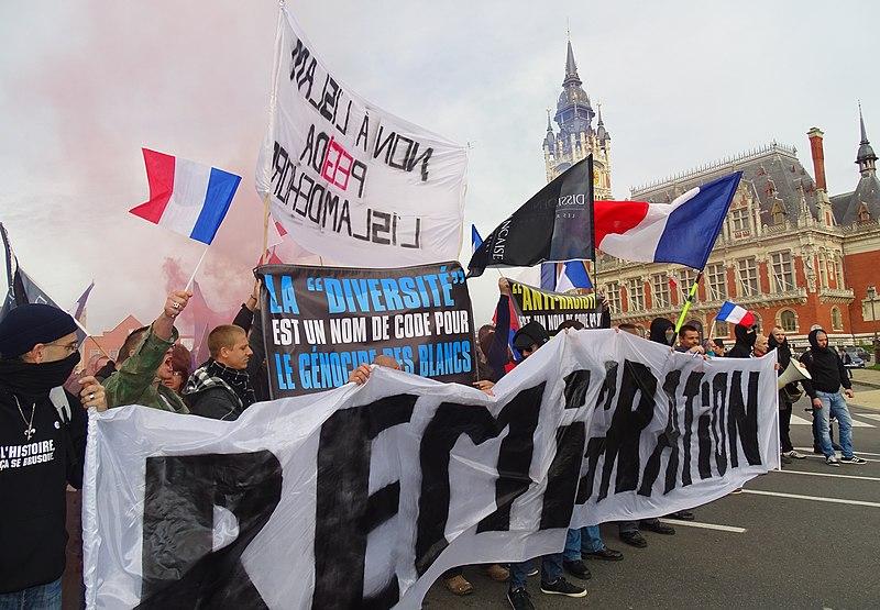 """Manifestantes anti-inmigrantes en Calais sostienen una pancarta que dice """"La diversidad es una palabra clave para el genocidio de los blancos"""". Autor: Jérémy-Günther-Heinz Jähnick , 08/11/2015. Fuente: Wikimedia Commons"""