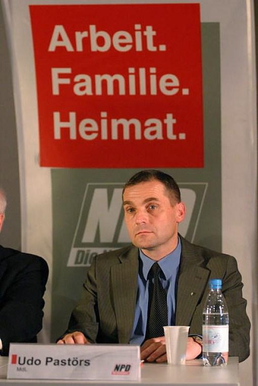 """Udo Pastörs, con un eslogan del partido ultraderechista NPD al fondo: """"Trabajo, Familia, Patria"""". Autor: Marek Peters, 26/06/2013. Fuente: Wikimedia Commons"""