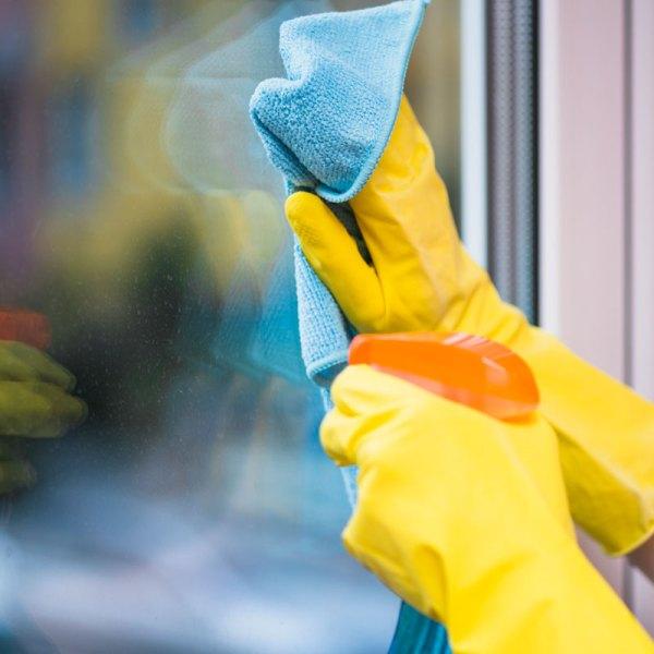 Limpiando una ventana con limpiavidrios Aldex.